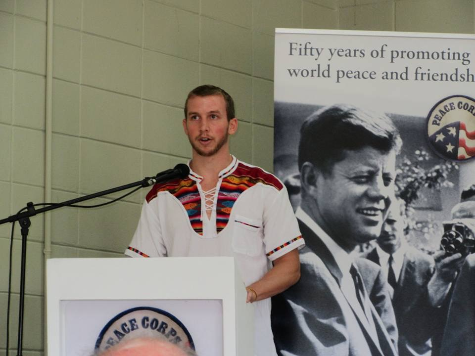 Trevor Johnson speaks at a podium next to a Peace Corps poster of John F. Kennedy.