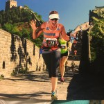 Vanden Bosch waves to the camera as she runs by on the Great Wall of China