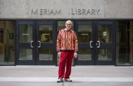 "Joe Crotts posing for a photo in front of the ""Meriam Library"" sign in front of the library entrance."
