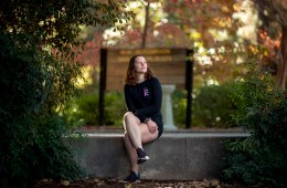 Zada Evans sits on a concrete wall under a canopy of trees.