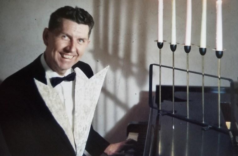 Robert Laxson sits at a piano while wearing a tuxedo.