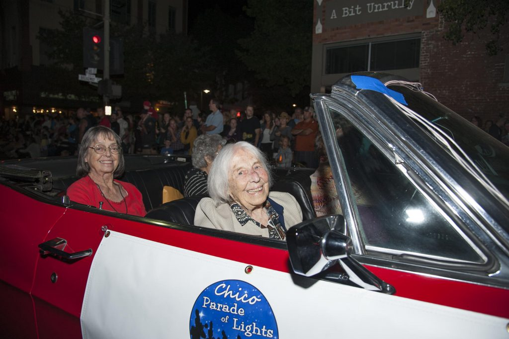 "Lynn Balmer in the front passenger seat of a convertible with signage that says ""Chico Parade of Lights."""