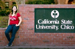 Student poses next to the California State University, Chico, sign.