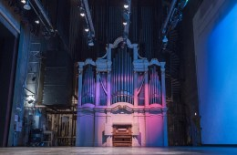 A large and ornate organ sits on a stage with dramatic lighting.