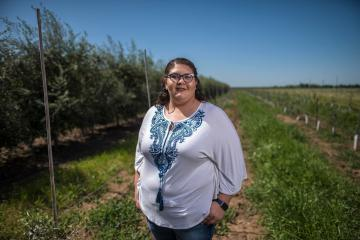 Stephanie Alvarado stands next to an olive orchard at the University Farm
