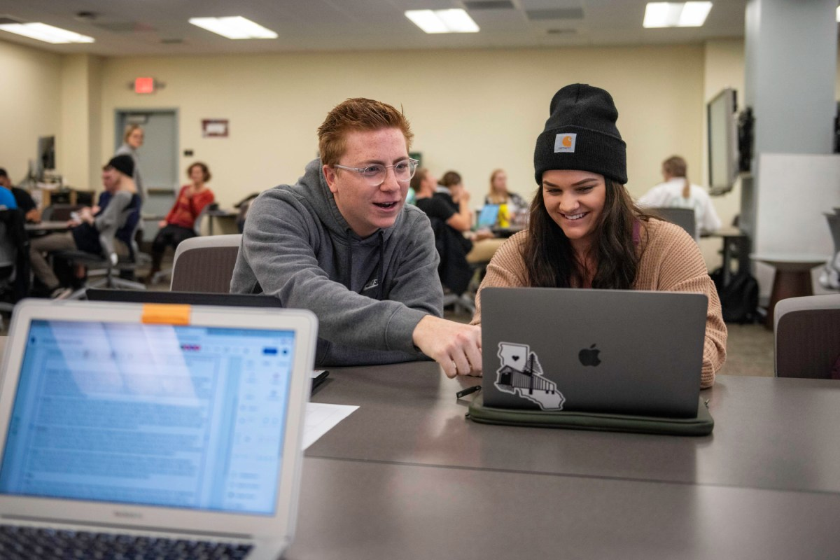 A student gestures to the screen of another student's laptop.