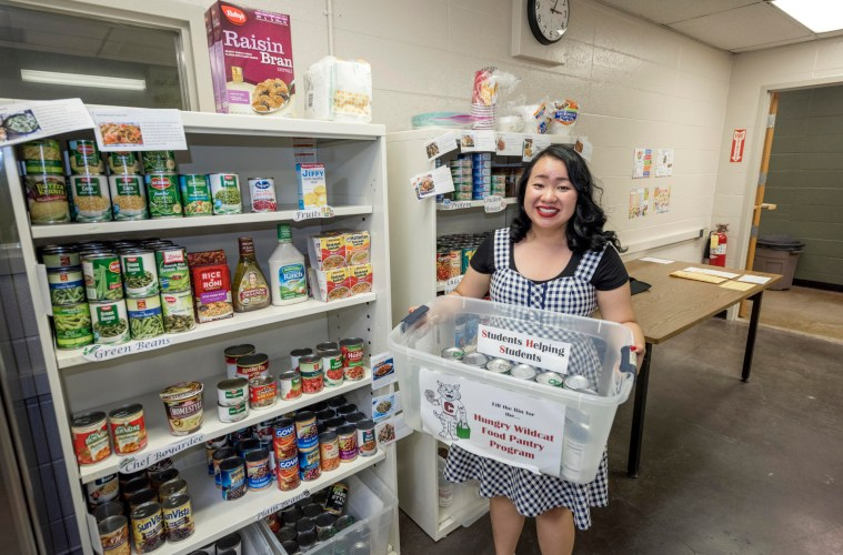Yee Yang holds up some of the food that the Hungry Wildcat Food Pantry provides nutritious food, CalFresh food program assistance and referral services for students experiencing food insecurity.