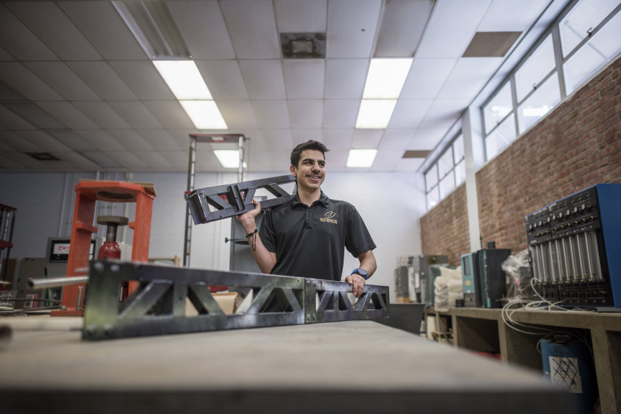 Alhumaidi holds parts of the steel bridge that he helped construct for a competition.