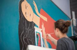 Autumn Robertson paints a mural of a woman on a campus wall.
