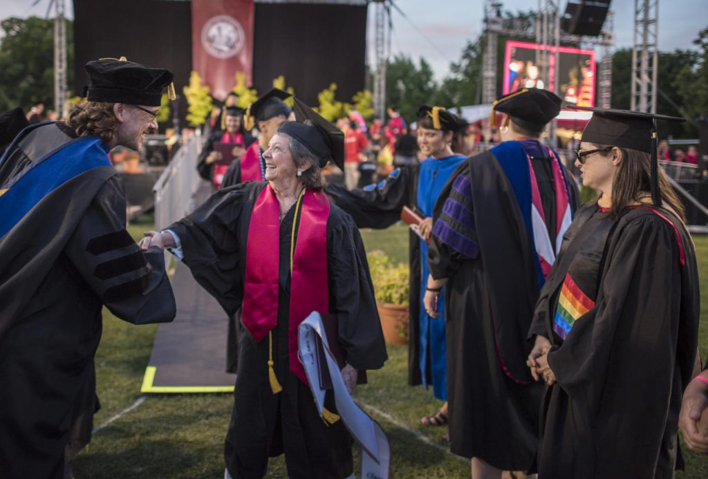 Sylvia Hamilton shakes hands with faculty after walking the stage.