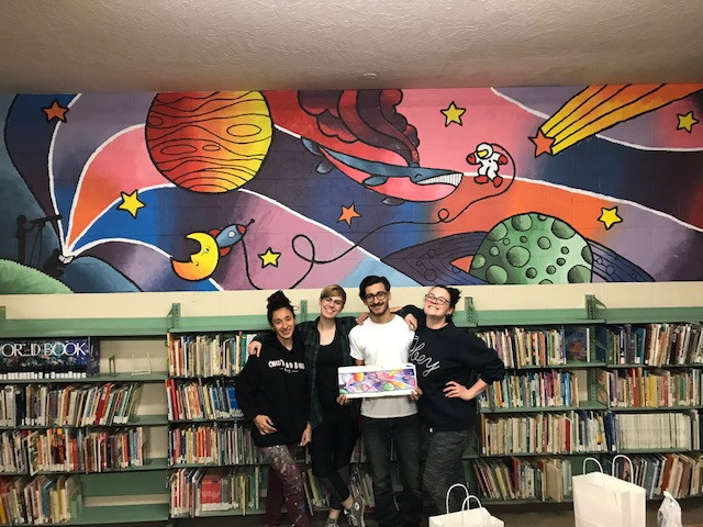 Four students stand in front of a bookshelf and a mural of space-themed art.