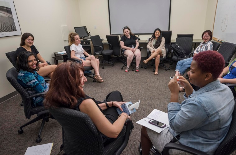 The women sit in a circle talking during the weekly meeting.