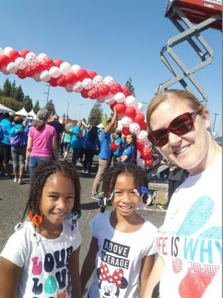 """Ashley Casey wears a T-shirt reading """"life is why"""" and poses for a photo next to two young girls, with an arch of balloons in the background."""