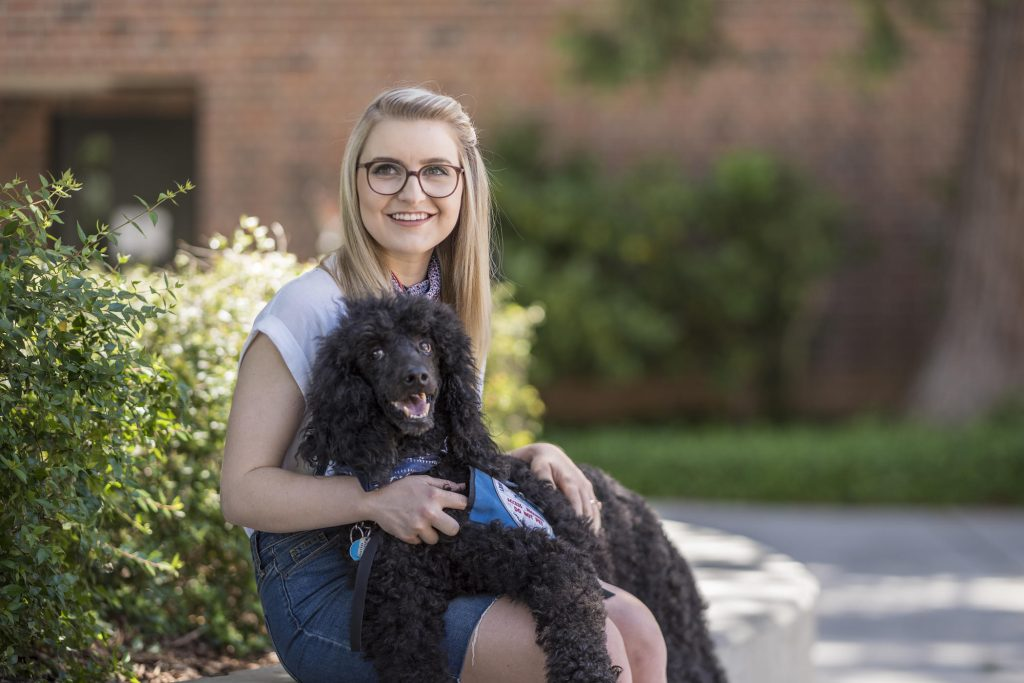 Coutts' service dog, Davy, was trained to smell hormones that signaled an oncoming seizure, as well as laying on Coutts (as he is here) to hit pressure points to prevent seizures.