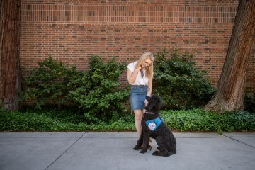 Taylor Coutts looks down at her service dog Davy