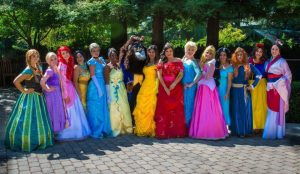 Women in Disney character costumes pose for a photo.