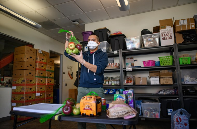 A food pantry worker wears a mask and rubber gloves as he shows off the options available.