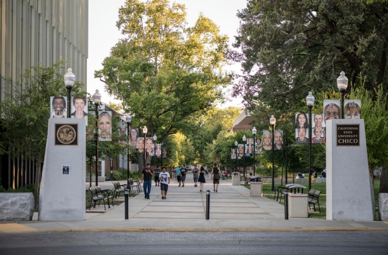 The southeast entrance to campus shows the faces of students, faculty, and staff on pole banners.