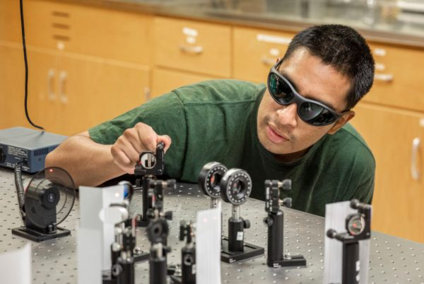 Eddie Cruz, wearing protective glasses, adjusts laser instruments on a tabletop.