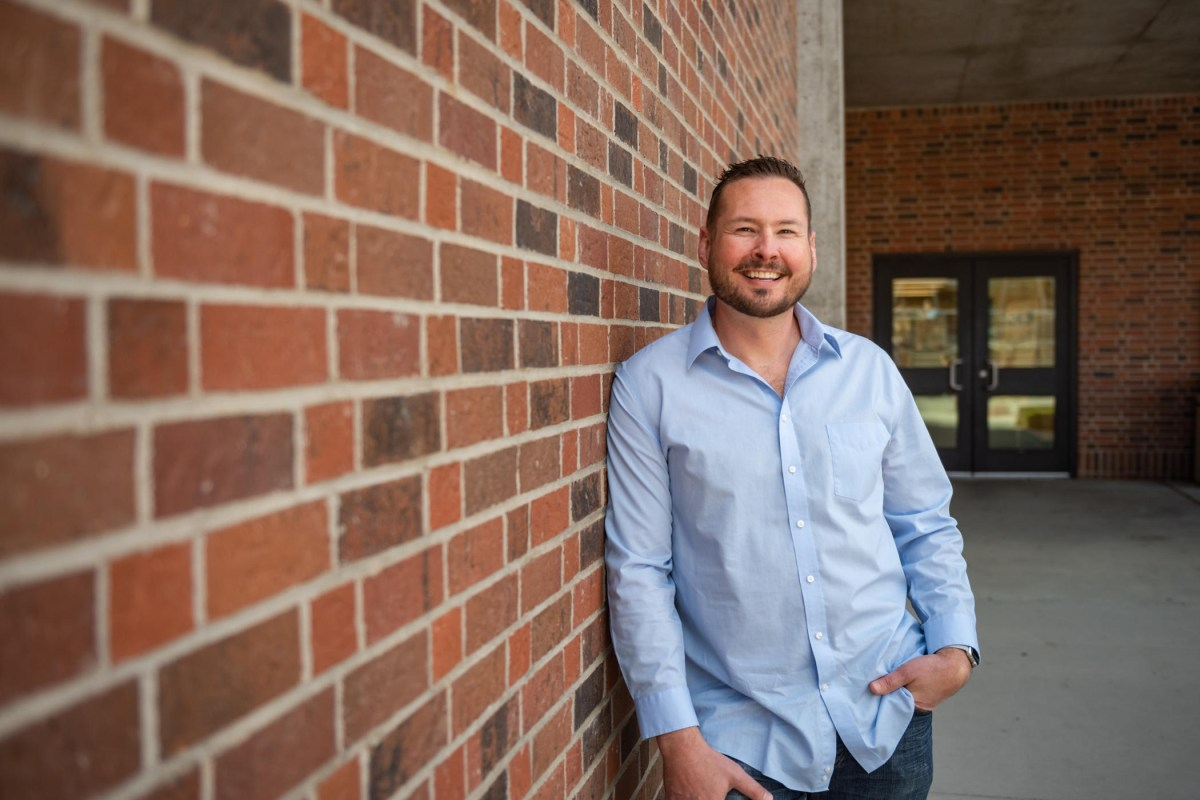 Slade Giles poses for a portrait near a brick wall.