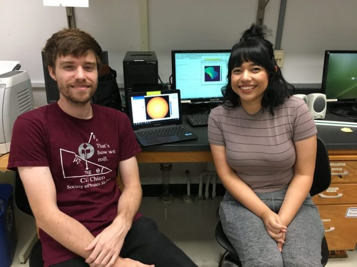 Two students pose for a photo near research computers.