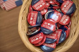 "A basket filled with brightly colored buttons sits on a table at Chico State. The buttons say, ""We Love Our Veterans."""