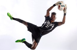 Damion Lewis jumps to catch a soccer ball during a photoshoot