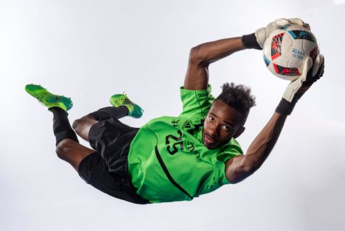 Damion Lewis jumps through the air to catch a soccer ball in a photo studio.