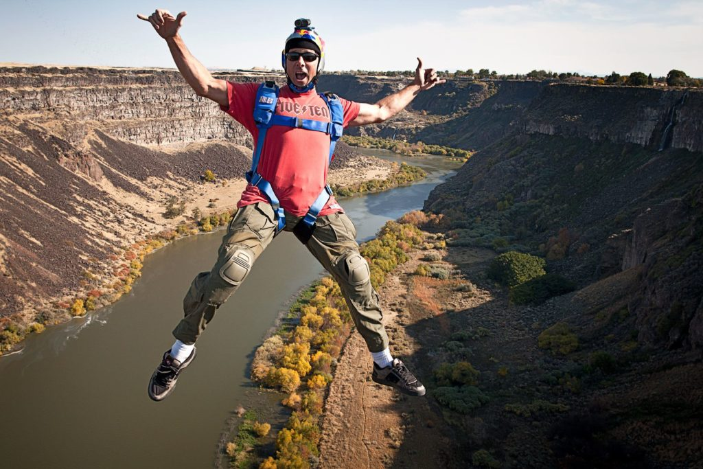Miles Daisher falls through the air, gesturing to the camera, as he BASE jumps over a river off the 486-foot-high I.B. Perrine Bridge in Twin Falls, Idaho.