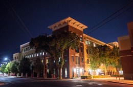 The Student Services Center is photographed at night. Street lights illuminate the walkways around the building.