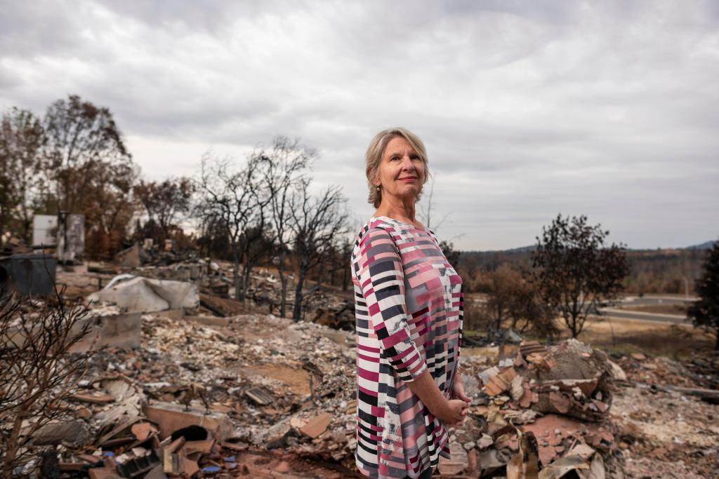 Shannon Phillip stands in the ruins of a home that was burnt to the ground by the Carr Fire.