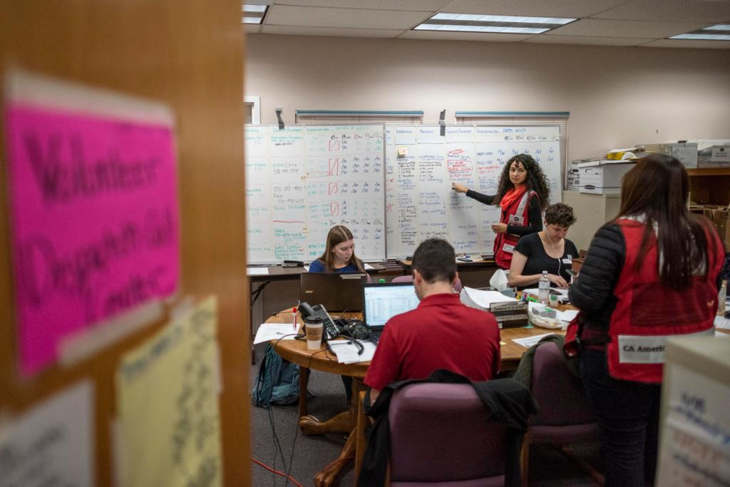 Volunteers work at computers and discuss items on a whiteboard in the Caring Choices volunteer center.