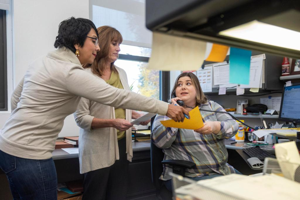 Lupita Arim-Law takes a piece of paper from Jessica Westbay in her cubicle, as Cindy Reiswig looks on.