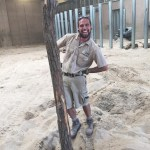 Portrait of Matthew Day in his zoo keeper uniform posing next to a tree branch stuck in the sand.