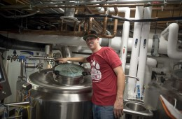 "Josh Leavy smiles as he brews Resilience IPA in a container reading ""San Francisco Brewing Co."""