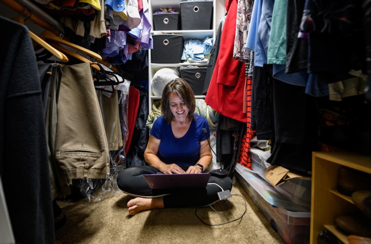 Marianna Paiva smiles as she works on her laptop on the floor of her closet.