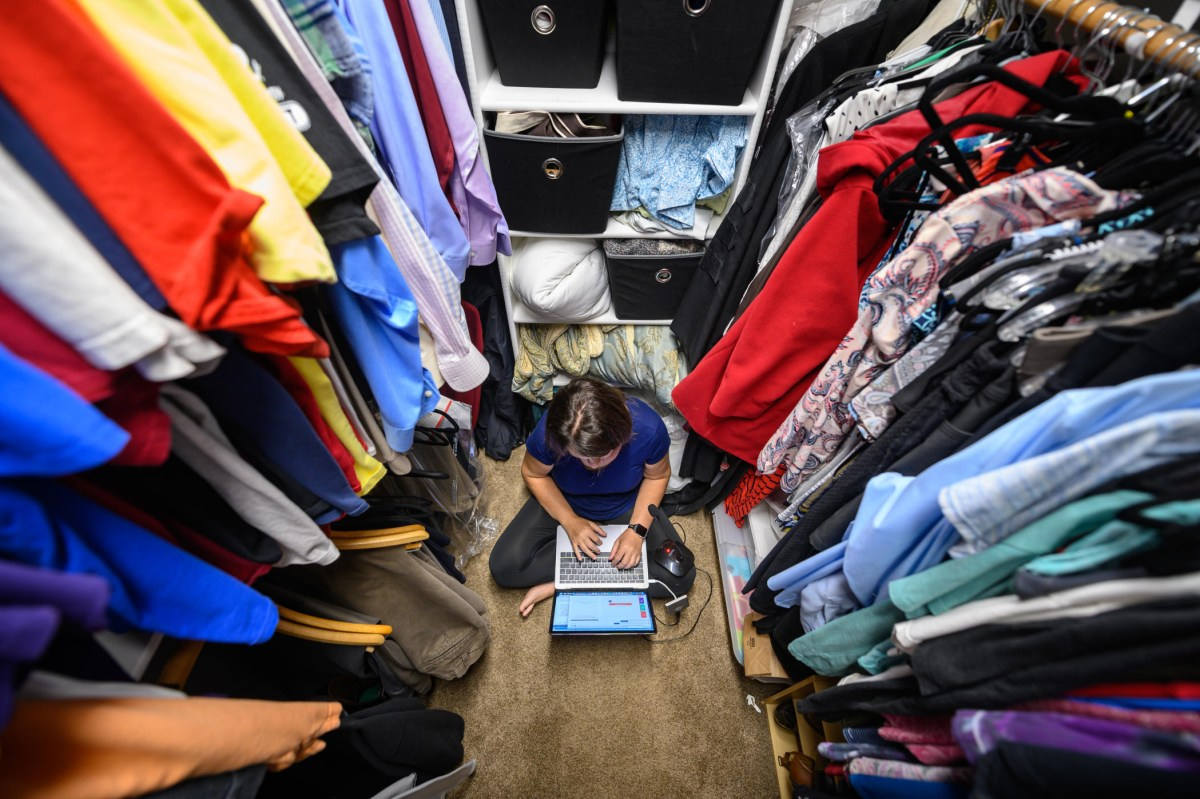 A view from near the ceiling looks down at Marianne Paiva in a closet filled with clothes.