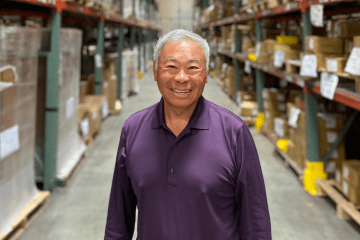 Portrait of Norman Tu standing in a warehouse