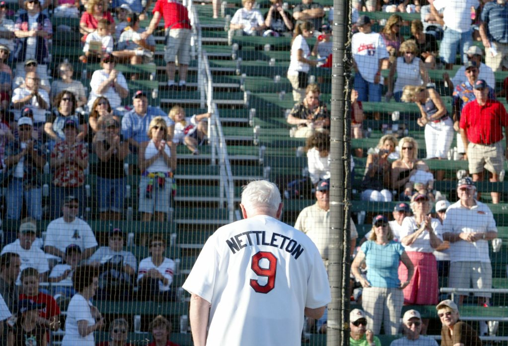 Nettleton, wearing a jersey with his name on it, gazes out at stands of fans from the batting area of Nettleton Stadium.