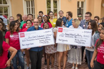 Students from the Student Philanthropy Council crowd behind Joe Picard and Kathleen Moroney as they both hold over-sized checks.