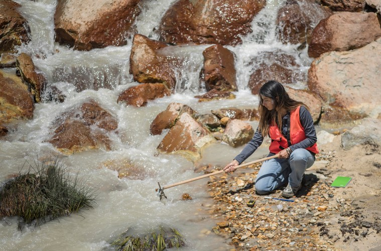 Angelica Rodriguez leans over a stream and collects a water sample.