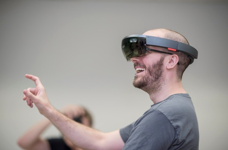Lance Mitchell extends his hand to touch his virtual surroundings while wearing the Microsoft HoloLens.