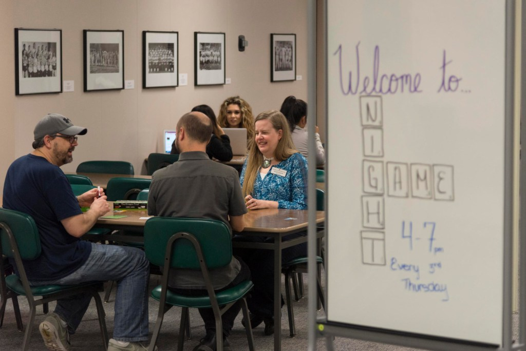 """A group of people sit at a table playing board games in the library. A white board sits next to the table and reads """"Welcome to Game Night."""""""