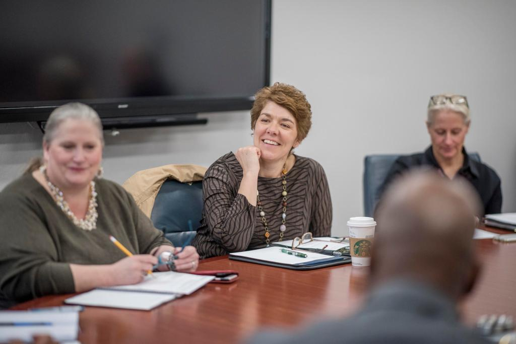 Barker smiles at others sitting with her at a conference table.