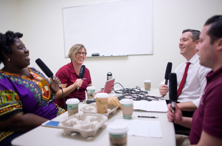 Tracy Butts, Mary Wallmark, Zach Justus, and Aaron Skaggs, (left to right) sit at a table and record the Caffeinated Cats podcast.