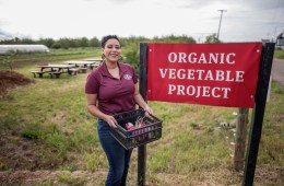 """Kaeli McCarther stands next to a sign that reads """"Organic Vegetable Project"""" while holding a crate of vegetables."""