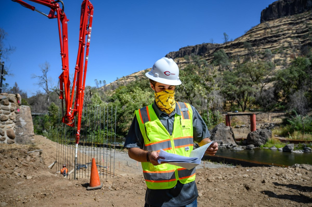 A student in a hard hat looks at engineering plans as heavy equipment is used in a bridge rebuild in a canyon behind him.