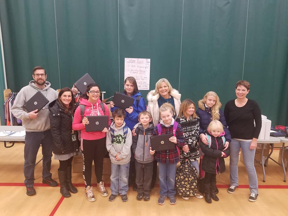 Brian Ausland and wife Jodi Halligan pose with a group of young students holding laptops.