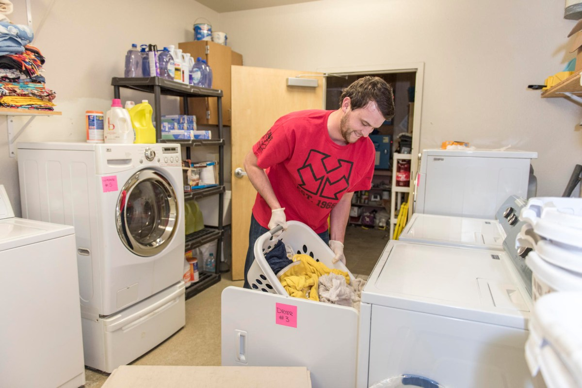 A student does laundry at a shelter serving individuals experiencing homelessness.