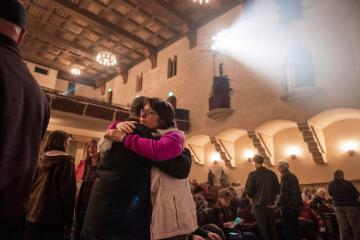 President Gayle Hutchinson shares a somber hug with someone as light shines through smoky air inside of Laxson Auditorium at a Camp Fire meeting.